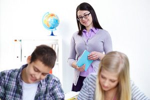 Portrait of happy teacher looking at lad and girl working at lesson