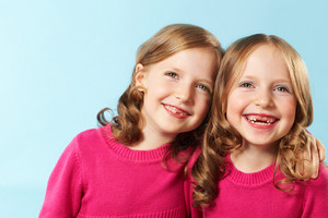 Portrait of happy twins laughing against blue background