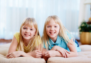 Portrait of happy twins looking at camera at home