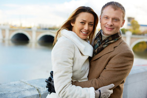 Portrait of happy urban couple embracing and looking at camera outside