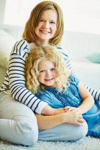 Portrait of happy woman and her daughter having rest at home