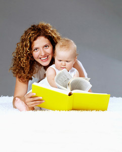 Portrait of happy woman and her daughter reading book on the floor