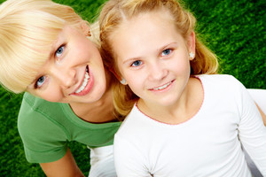 Portrait of happy woman embracing her pretty daughter and both looking at camera