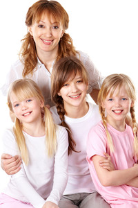 Portrait of happy woman embracing her three daughters
