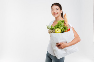 Portrait of happy woman holds fruit and vegetable. Isolated on white background.