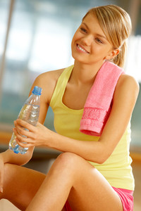 Portrait of happy woman wearing yellow tanktop looking aside with smile in gym