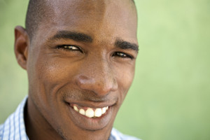 Portrait of happy young african american man looking at camera and smiling. Head and shoulders, copy space