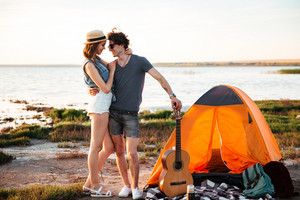 Portrait of happy young attractive couple embracing in front of camping tent
