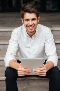 Portrait of happy young businessman using tablet computer outdoors
