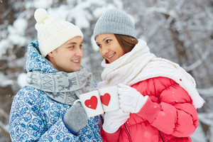 Portrait of happy young couple cheering up with drinks in winter park