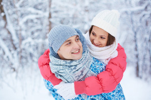Portrait of happy young couple having fun in winter park