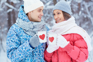 Portrait of happy young couple holding cups with red hearts in winter park