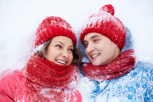 Portrait of happy young couple lying on snow and looking at one another
