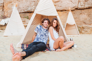Portrait of happy young couple sitting in teepee on the beach