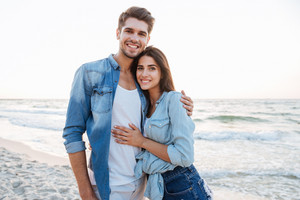 Portrait of happy young couple standing and hugging on the beach