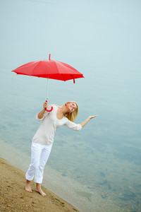 Portrait of happy young girl on the shore with umbrella