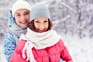 Portrait of happy young man embracing his girlfriend in winter park
