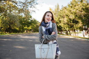 Portrait of happy young woman wearing scarf smiling against nature background and holding bag. Look aside.
