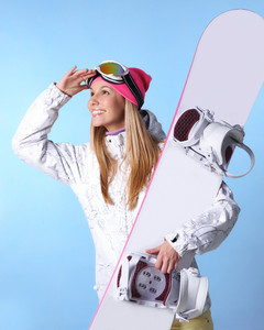 Portrait of healthy woman with pair of skis in hands looking somewhere