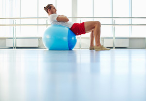 Portrait of healthy young man exercising with ball