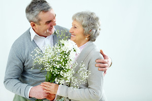 Portrait of husband giving bouquet of flowers to wife at Woman's day