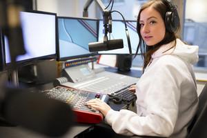 Portrait Of Jockey Using Headphones And Microphone In Radio Studio
