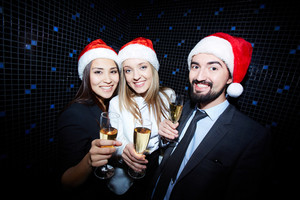 Portrait of joyful colleagues in Santa caps toasting with champagne in nightclub