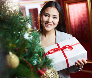 Portrait of joyful female with xmas present looking at camera with smile