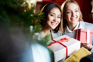 Portrait of joyful females giving xmas presents to their associate, one of them looking at camera