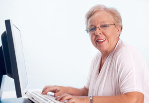 Portrait of kind and friendly woman typing and looking at camera