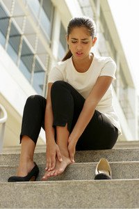 Portrait of latina woman walking on high heels and feeling pain, massaging feet with hand and sitting on stairs
