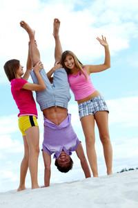 Portrait of laughing teenage friends having fun on sandy beach