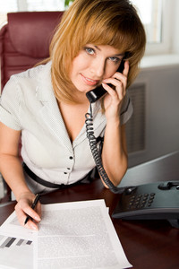 Portrait of lovely business lady calling by the phone in office and looking at camera