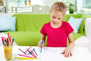 Portrait of lovely girl drawing with colorful pencils at home
