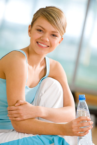 Portrait of lovely girl holding bottle of water in hand and smiling