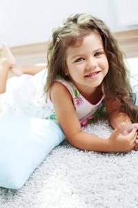 Portrait of lovely girl lying on the floor at home
