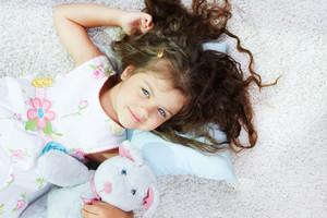 Portrait of lovely girl lying with teddybear