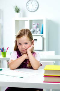 Portrait of lovely girl sitting at workplace in classroom