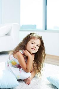 Portrait of lovely girl sitting on the floor at home