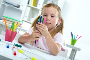 Portrait of lovely girl with colorful crayons looking at them