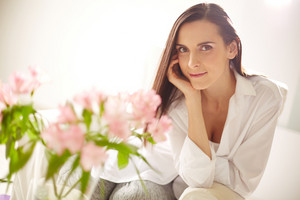 Portrait of lovely lady looking at camera with bunch of pink flowers in front