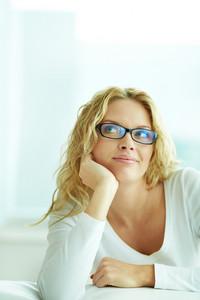 Portrait of lovely woman in eyeglasses posing for camera