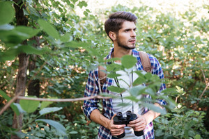 Portrait of male hiker in forest. man in shirt with binoculars and backpack looking away