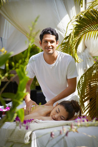 Portrait of masseur massaging young beautiful asian woman during beauty treatment in exclusive resort. Vertical shape, front view.