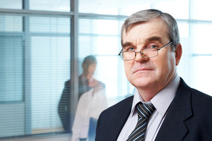 Portrait of mature boss in eyeglasses looking at camera