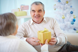 Portrait of mature man giving present to his wife