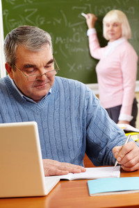 Portrait of mature man making notes on background of teacher standing by blackboard