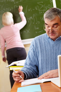 Portrait of mature man making notes on background of teacher writing on blackboard