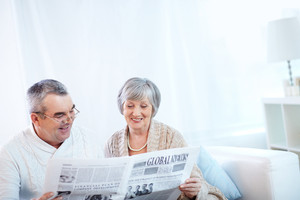 Portrait of mature woman and her husband reading newspaper together