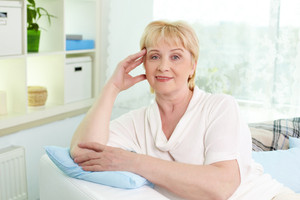 Portrait of mature woman looking at camera while having rest at home